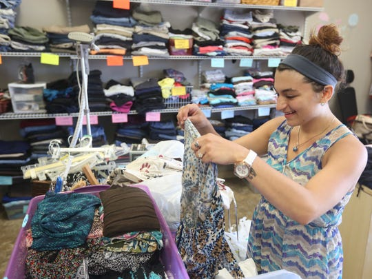 Florida Gulf Coast University student Alina Ossi sorts through clothes at Eva's Closet. The psychology major began an internship in January and has quickly decided to specialize in social work after spending time with Goodall and the many families in need of help.