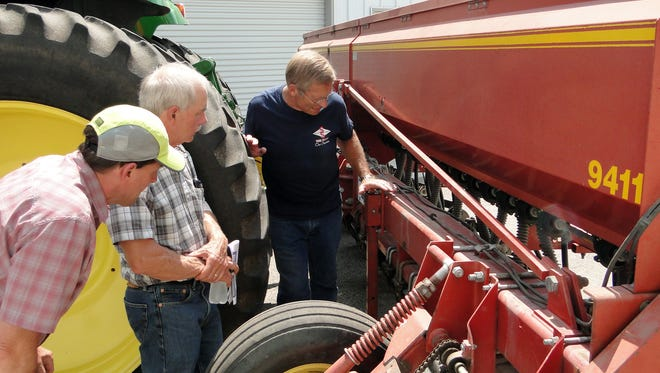 Farmers look at the various adjustments Marty Weiss made on his drill in order to establish cover crops on his Beaver Dam farm.  Dodge County offers help to farmers needing assistance in calibrating their drills or setting them up for this specialized work.