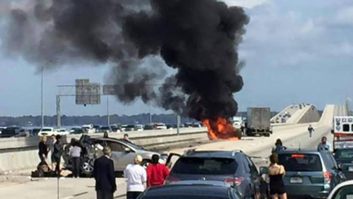 Drivers look on as an SUV burns following a crash on