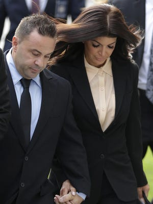"""FILE- In this Oct. 2, 2014 file photo, """"The Real Housewives of New Jersey"""" stars Teresa Giudice, and her husband Giuseppe """"Joe"""" Giudice, left, of Montville Township, N.J., walk toward Martin Luther King Jr. Courthouse for a court appearance on federal conspiracy and bankruptcy fraud charges in Newark, N.J. An attorney for Joe Giudice said the husband of Teresa Giudice, is expected to report to the Fort Dix federal prison on Wednesday, March 23, 2016, to begin serving a 41-month sentence for bankruptcy fraud. (AP Photo/Julio Cortez, File)"""