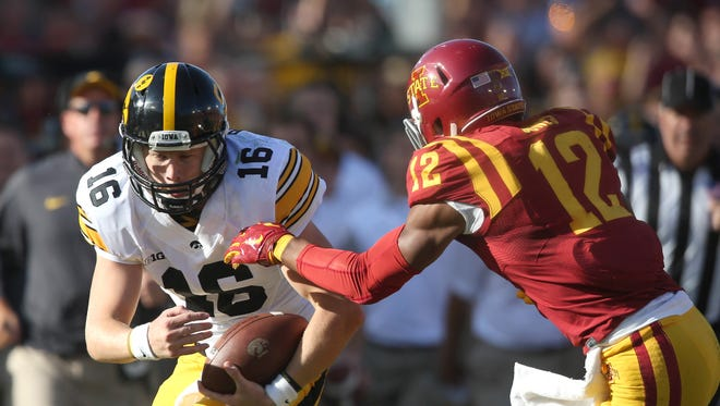 Iowa quarterback CJ Beathard braces for the hit by Iowa State linebacker Jay Jones after running the ball for a first down during the Cy-Hawk series on Saturday at Jack Trice Stadium in Ames, Iowa.