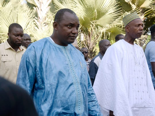 Gambian President-elect Adama Barrow, center, flanked