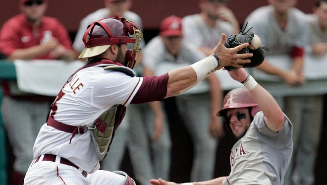 Alabama's Mikety White beat the throw to home and slides under the tag of Florida State's Danny De La Calle in the seventh inning of an NCAA regional baseball game on Saturday in Tallahassee, Florida. Alabama won the game 6-5.