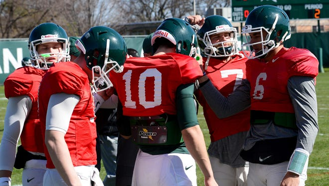 The five Spartan quarterbacks gather together in-between drills as the Spartan football team practices Tuesday, April 6, 2016, at the  John and Becky Duffey Football Practice Fields on the campus of Michigan State University.