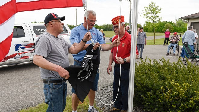 Duane Bendorf, left to right, Tim Coil, Coil's Flags and Flagpoles, and LeRoy Leither get ready to raise the flags up the new flag pole Friday, May 20, at Granite Ridge Village in Waite Park. Charlie Bendorf wanted to honor his father and other veterans in the senior living facility with a large American flag and pole.