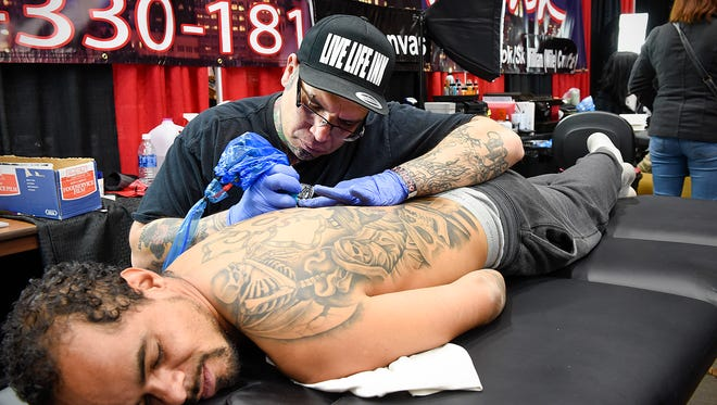 Mike Vazquez, Skin City Ink, Oak Dale, creates a tattoo on the back of Jorelle Haines at the Cloud-A-Scope Tattoo and Arts Convention Saturday, Nov. 12, at the Rivers Edge and Convention Center. Artists from around the country create and show their best work for judges.