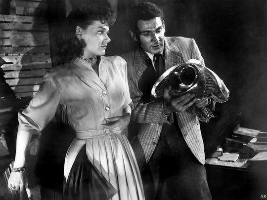 "Ann Robinson and Gene Barry examine a piece of alien technology in ""The War of The Worlds""."