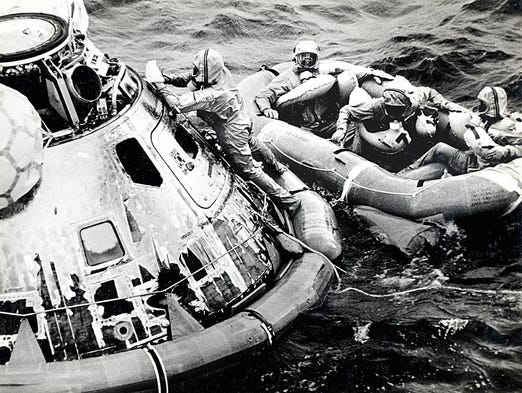 July 24, 1969--Looking on as Navy SEAL Clancy Hatleberg closes the capsule?s hatch, astronauts Michael Collins, Neil Armstrong (center) and ?Buzz? Aldrin, sit in their life raft.  While still inside the cramped capsule, the astronauts changed into their Biological Isolation Garments (shown here).   The recovery helicopter will soon hoist them aboard and rush them to the aircraft carrier USS Hornet.  During recovery, I shoot 8 rolls of color film. It is now in the NASA archive and website.   Photo by Milt Putnam