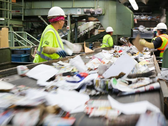 Workers pick through paper goods after they have been