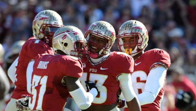 Florida State Seminoles defensive back Jalen Ramsey (13) celebrates an interception with defensive back Terrence Brooks (31) during the first quarter of the game against the North Carolina State Wolfpack at Doak Campbell Stadium.