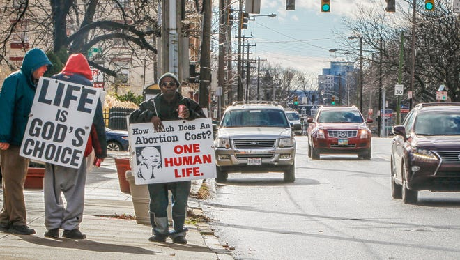 Protestors of abortion stand outside the Planned Parent building with signs on Auburn Street Monday December 14, 2015.