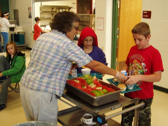 A representative from the Farm to School program serves locally grown watermelon to a couple fifth-grade students at Madison school.