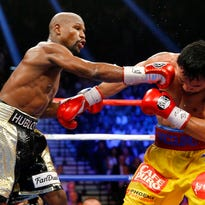 Floyd Mayweather Jr. (left) connects against Manny Pacquiao during their welterweight unification bout on May 2, 2015 at the MGM Grand Garden Arena in Las Vegas, Nevada. Mayweather remains undefeated after a unanimous decision.