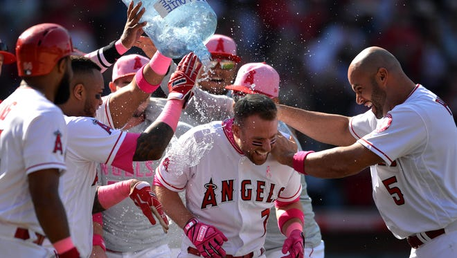 Los Angeles Angels third baseman Zack Cozart is doused with water after hitting a walk-off RBI single during the ninth inning to defeat the Minnesota Twins 2-1 at Angel Stadium of Anaheim.