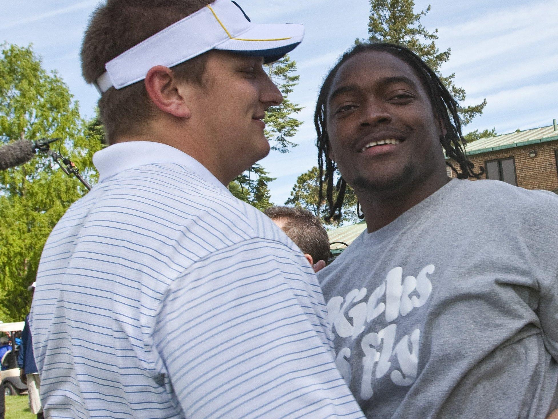 Former Michigan football players Jake Long, left, and Pierre Woods greet each other before a golf tournament in 2010 in Ann Arbor.
