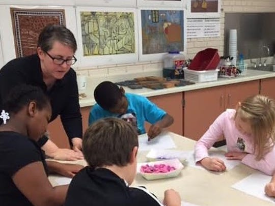 "Artist-in-residence Mel Kolstad works with students at Rosenow Elementary School on a project that involves sandpaper and learning about having ""grit."""