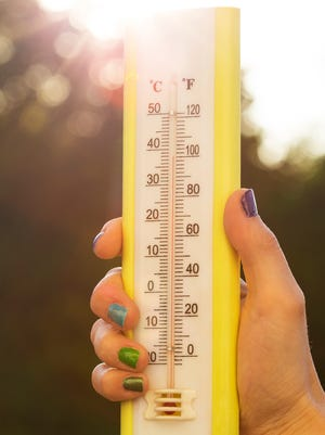 Hand holding a thermometer in air.