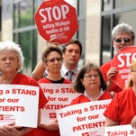 In this June 2013 file photo, nurses gather during a protest at the Anderson House Office Building in downtown Lansing. One year after more low-income adults in Michigan became eligible for Medicaid under the federal health care law, enrollment is skyrocketing near 600,000, well above initial projections.