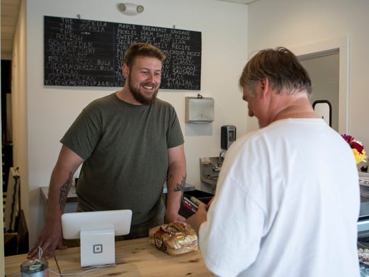 Jeff Marquardt (left) serves one of the shop's customers. On some days, the shop sells out of sausage or comes close to it.