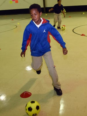 Julius Patrick Elementary School student Danny Moore runs through soccer drills led by Crossroads Soccer Association on Friday. Students in third through fifth grades with fewer than 10 behavior infractions were allowed to participate in electives such as cooking, art, soccer, football or cheerleading. The electives are rewards for good behavior.