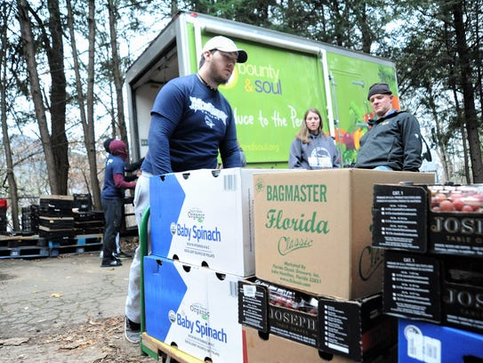 Gabe deBeus, a junior for the Montreat College lacrosse team, wheels produce into Bounty & Soul in Black Mountain during Cavalier Care Day on Dec. 6.