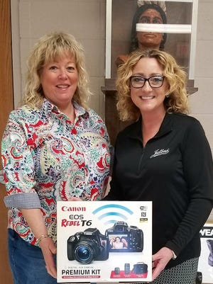 Adviser Sandy Wilhite accepts the new Canon T6 camera package from Jostens Representative Stacy Harrington.