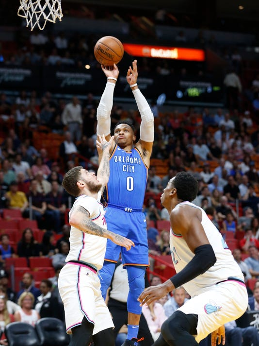 Oklahoma City Thunder guard Russell Westbrook (0) shoots against Miami Heat guard Tyler Johnson, left, and center Hassan Whiteside (21) during the first half of an NBA basketball game, Monday, April 9, 2018, in Miami. (AP Photo/Wilfredo Lee)
