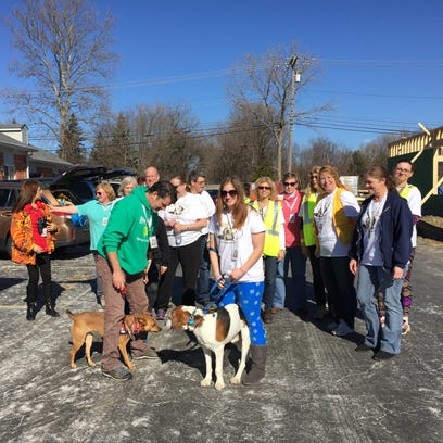 Cynthia Booth, center, with her foster dog Klaus, and