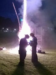 Workers light off fireworks during a break in the rain