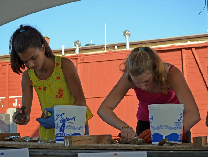Malayshia Andrews, 12, of Millville, and Selena Conley, 13, of Laurel Lake compete in the amateur oyster shucking contest at Bay Day on Saturday. Photo/Jodi Streahle