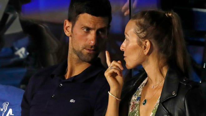 In this Sunday, June 14, 2020 file photo Novak Djokovic, left, speaks with his wife Jelena during a final match of the Adria Tour charity tournament, between Dominic Thiem and Filip Krajinovic, in Belgrade, Serbia. Djokovic has tested positive for the coronavirus after taking part in a tennis exhibition series he organized in Serbia and Croatia. The top-ranked Serb is the fourth player to test positive for the virus after first playing in Belgrade and then again last weekend in Zadar, Croatia. His wife also tested positive.