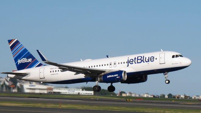 A JetBlue Airways plane landing on a runway
