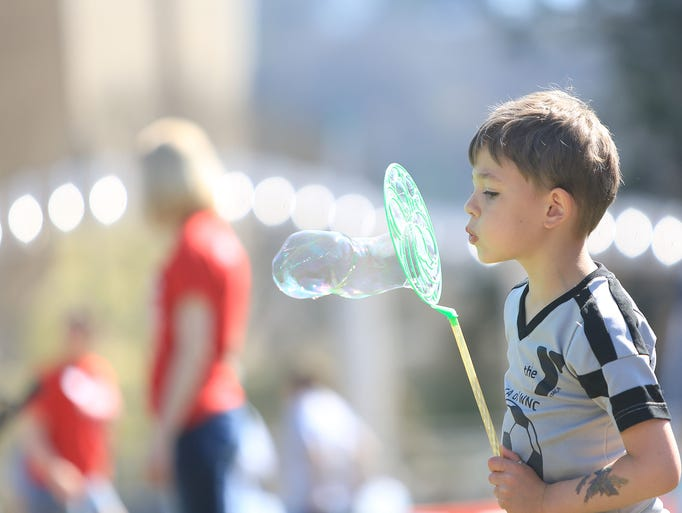 Micah Hopkins of Asheville; age 4, blows bubbles during the YMCA's Healthy Kids Day on Saturday afternoon at Pack Square Park.  The event featured a parade, music and performances, local food, and games for children.   -4-12-14 Colby Rabon (colbyrabon@gmail.com)