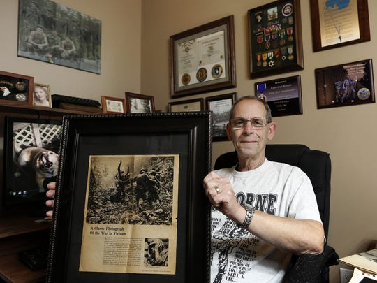 Veteran John Vandehaar holds up a copy of an iconic Vietnam War photo, shot by Associated Press photographer Art Greenspon, that Vandehaar had framed and displayed in his home office in Des Moines. Though Vandehaar is not in the photo, he experienced similar combat scenarios.