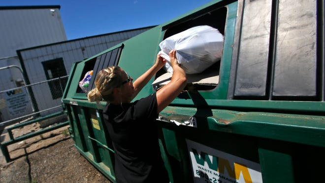 Jennifer Malone drops off items on Monday at Waste Management's Recycling Center in Farmington. Farmington officials are looking at slightly increasing residents' trash rates to cope with a downturn in the recycling industry.