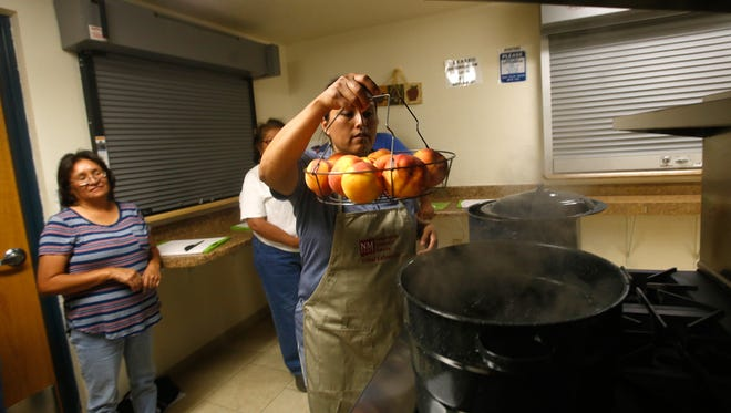 Home economist Leah Platero blanches a batch of peaches Friday during a canning workshop at the Nenahnezad Harvest Festival at the Nenahnezad Chapter House.