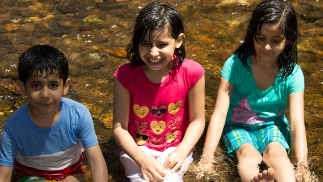 Wisam Abu-HJaze (left), Fagar Abu-HJaze (center) and Sham Abu-HJaze (right) play in the water at Caledonia State Park the afternoon of June 30.