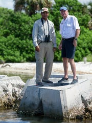 "Audubon Florida sanctuary manager Mark Rachal, left, and Living Shoreline Solutions CEO Thomas Brown stand on one of Brown's company's wave attenuation devices, or WADs, installed at Sunken Island in Tampa Bay. WADs are hollow concrete pyramids that Brown says ""Kill wave energy to stop erosion."""