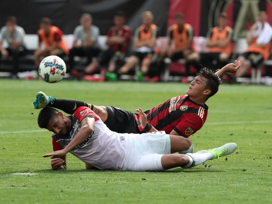 Atlanta United forward Brandon Vazquez, right, fights for the ball with D.C. United defender Sean Franklin in the second half of their game at Bobby Dodd Stadium at Historic Grant Field in Atlanta.