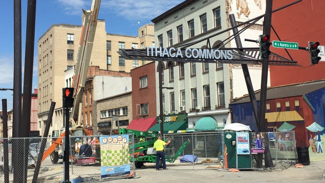Workers installed the new Ithaca Commons sign on Friday morning.