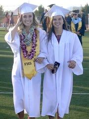 Sara Miller (left) and Hailee Edgar walk toward commencement.