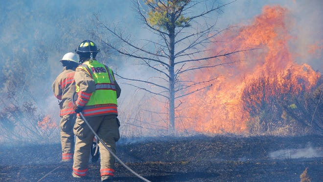Firefighters worked to contain a brush fire Saturday.