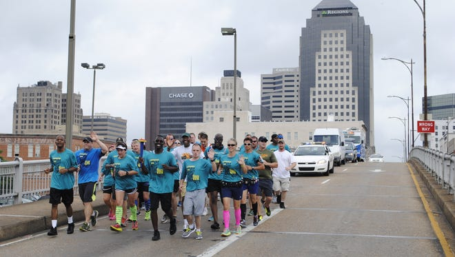 Members of Shreveport Police Department and Caddo Parish Sheriff's Office assist in carrying the Flame of Hope for the Special Olympics.