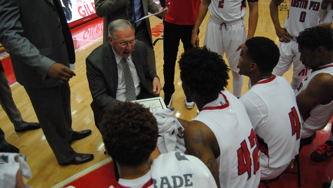 Longtime coach Dave Loos goes over a play with his team during a timeout.