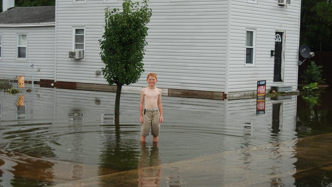 Floodwater rises almost to the knees of a child in Crisfield after overnight storms caused floods on Thursday, Sept. 29, 2016.