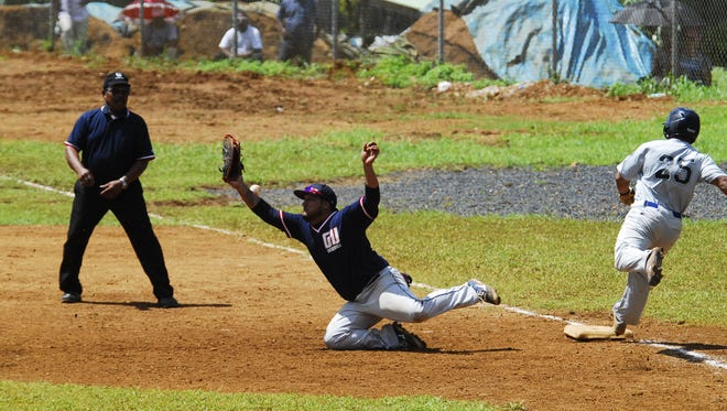 In this file photo, a throw gets past Guam first baseman Randy Alcantara to put a runner on for the Commonwealth of Northern Mariana Islands in their baseball game at the 8th Micronesian Games in Pohnpei.