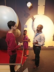 Yashua Kumar and Victoria Cameron, students participating in the junior docent program at the Hudson River Museum in Yonkers, listen to Marc Taylor, manager of the planetarium and science programs as he describes his plans for the New Horizon - Pluto exhibition. The students will help with the installation.