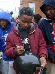 Eighth-grader Jordyn Williams, 15, writes a message on a balloon during an event at Parkway Academy North in Wilmington on Friday. Students released balloons to address violence in the community.