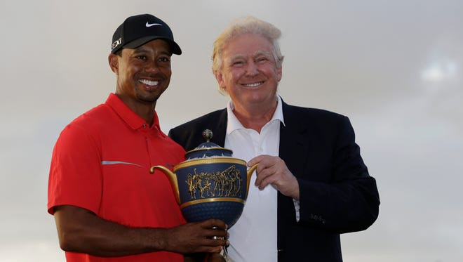 In a file phote from 2013, Tiger Woods stands with Donald Trump as he holds the Gene Serazen Cup for winning the Cadillac Championship in Doral, Fla.