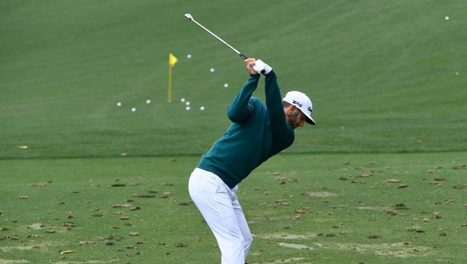 Dustin Johnson hits on the practice range April 6 before withdrawing from the Masters with a back injury.